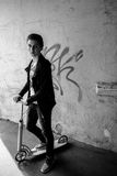 Portrait d'un garçon sur le scooter dans la rue urbaine Photos stock