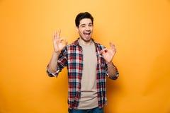 Portrait d'un geste joyeux d'ok de showng de jeune homme photo stock