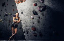 Portrait d'un grimpeur féminin gai se penchant sur un mur bouldering au gymnase photos libres de droits