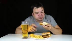 Portrait d'un gros hamburger mangeur d'hommes avide sur le fond noir banque de vidéos