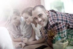 Portrait d'un groupe d'étudiants travaillant sur un ordinateur portable Photos stock