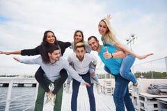 Portrait d'un groupe des jeunes s'asseyant au bord du pilier, dehors en nature Amis appréciant un jeu sur Images stock