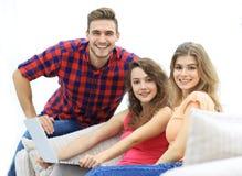 Portrait d'un groupe des jeunes s'asseyant sur le divan dans le salon Photo libre de droits