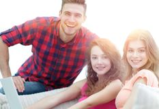 Portrait d'un groupe des jeunes s'asseyant sur le divan dans le salon Photo stock