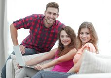 Portrait d'un groupe des jeunes s'asseyant sur le divan dans le salon Images libres de droits