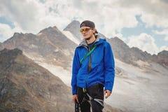 Portrait d'un guide professionnel d'un alpiniste dans un chapeau et des lunettes de soleil avec une hache de glace dans sa main c photo libre de droits