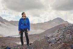 Portrait d'un guide professionnel d'un alpiniste dans un chapeau et des lunettes de soleil avec une hache de glace dans sa main c photographie stock libre de droits