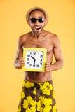 Portrait d'un homme africain dans les vêtements de bain tenant l'horloge murale Images stock