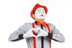 Portrait d'un homme, artiste, clown, MIME Montre un coeur d'isolement dessus images stock