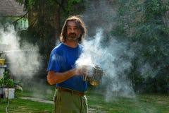 Portrait d'un homme avec de la fumée contre la lumière du soleil de matin photographie stock