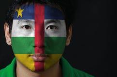 Portrait d'un homme avec le drapeau du centrafricain peint sur son visage sur le fond noir image libre de droits