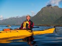 Portrait d'un homme avec une barbe se reposant dans un kayak sur le fond d'une grande montagne et d'un ciel bleu Images stock