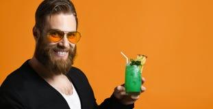 Portrait d'un homme barbu charismatique dans des lunettes de soleil avec un cocktail dans des ses mains photographie stock