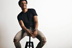 Portrait d'un homme bel dans la séance noire de T-shirt Photographie stock