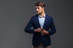Portrait d'un homme bel occasionnel boutonnant sa veste images stock