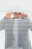 Portrait d'un homme d'affaires jetant un coup d'oeil par des abat-jour dans le bureau Photos stock