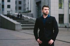 Portrait d'un homme d'affaires sérieux dans un costume foncé et une barbe contre le contexte de l'architecture moderne Photo stock