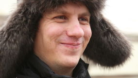 Portrait d'un homme dans le chapeau de fourrure d'hiver banque de vidéos