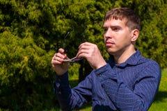 Portrait d'un homme dans les lunettes de soleil et la position bleue de chemise ext?rieures en parc photographie stock