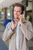 Portrait d'un homme de sourire employant le sien téléphone Photo stock