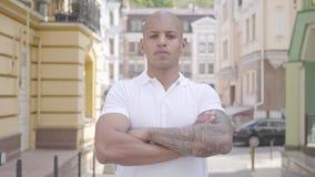 Portrait d'un homme du Moyen-Orient chauve réussi sûr utilisant un T-shirt blanc regardant la caméra Mouvement lent clips vidéos