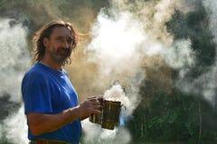 Portrait d'un homme entouré par la fumée contre la lumière du soleil de matin images libres de droits