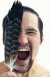 Portrait d'un homme fâché criant avec la plume et des yeux fermés Photo stock