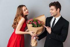 Portrait d'un homme gai donnant son bouquet de fleur d'amie Photos libres de droits