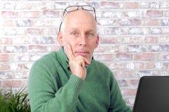 Portrait d'un homme mûr bel à l'aide de l'ordinateur portable Photographie stock
