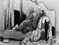 Portrait d'un homme s'asseyant sur un divan (toutes les personnes représentées ne sont pas plus long vivantes et aucun domaine n' Photos libres de droits