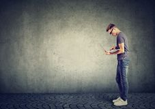 Portrait d'un homme se tenant utilisant son ordinateur portable Photos libres de droits