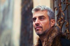 Portrait d'un homme sexy dans la fourrure de loup et la fenêtre médiévale ornementale sur le fond Images libres de droits