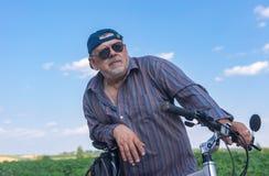 Portrait d'un homme supérieur barbu et potelé étant prêt au tour d'été sur une bicyclette Photographie stock