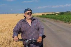 Portrait d'un homme supérieur barbu et potelé étant prêt pour monter sur une bicyclette Images libres de droits