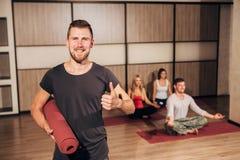 Portrait d'un homme tenant le tapis de yoga et montrant des pouces  Photographie stock
