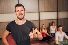 Portrait d'un homme tenant le tapis de yoga et montrant des pouces  Photos stock