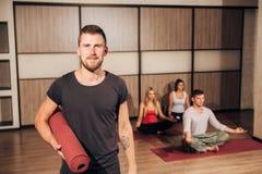 Portrait d'un homme tenant le tapis de yoga et souriant avec sa main derrière la tête Images stock