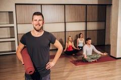 Portrait d'un homme tenant le tapis de yoga et souriant avec sa main derrière la tête Images libres de droits