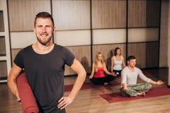 Portrait d'un homme tenant le tapis de yoga et souriant avec sa main derrière la tête Photo libre de droits