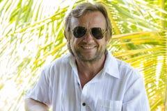 Portrait d'un homme d'une cinquantaine d'années non rasé dans des lunettes de soleil détendant sur la nature dans le jour d'été Photographie stock libre de droits