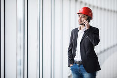 Portrait d'un ingénieur parlant au téléphone contre les fenêtres panoramiques Image libre de droits