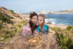 Portrait d'un jeu religieux de Pâques avec deux filles dans les costumes des oiseaux se reposant près d'un nid énorme avec des oe Images stock