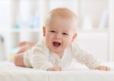 Portrait d'un jeune bébé mignon utilisant une chemise de combinaison se trouvant sur le ventre dans la chambre de crèche Images stock