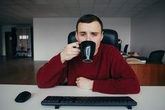 Portrait d'un jeune café potable fatigué d'employé de bureau au travail La situation dans le bureau Image libre de droits