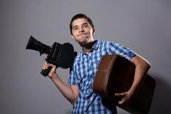 Portrait d'un jeune cameraman avec le vieil appareil-photo de film et un suitca Photos libres de droits