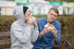 Portrait d'un jeune couple affamé qui mangent des hamburgers en parc sur un banc et un sourire image libre de droits