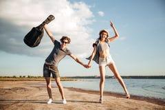 Portrait d'un jeune couple ayant l'amusement sur la plage Photo stock
