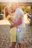 Portrait d'un jeune couple de famille étreignant des baisers dans les taches de lumière du soleil Photos libres de droits