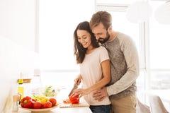 Portrait d'un jeune couple de sourire dans la cuisson d'amour Images libres de droits