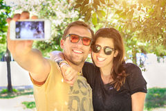 Portrait d'un jeune couple de touristes attrayant utilisant un smartphone pour prendre une photo de selfie, ayant l'amusement émo Photographie stock